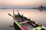 Traditional Rowing Boat Moored on the Edge of Flat Calm Taungthaman Lake at Dawn
