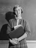 Teenage Girl Holding School Books Standing in Front of Blackboard