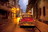 Red Vintage American Car Parked on a Floodlit Street in Havana Centro at Night