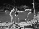 Two Women Pulling Man into Woodland Swimming Pond All Wearing Bathing Suits