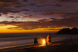 People with Driftwood Fire at Sunset on Playa Guiones Beach