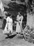 Two Women Talking in Yard One Holding Garden Hoe the Other Holds Basket with Flowers