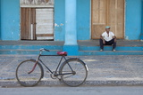 Old Bicycle Propped Up Outside Old Building with Local Man on Steps Papier Photo par Lee Frost