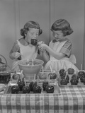 Two Twin Girls Eating Making Candy Apples in Kitchen