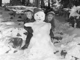 1950s-1960s Smiling Boy and Girl Building a Snowman Together in Snowy Woods
