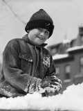 1920s-1930s Smiling Boy Playing in Snow Making Snowball