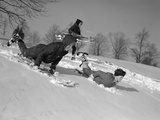 1960s 3 Boys Sledding Running Down Hill in Winter Snow