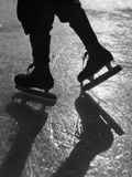 1930s Silhouette Figure Shown from Knees Down Wearing Ice Skates Skating in Ice Sun Glare