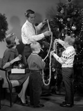 1960s Family Father Mother Two Sons Trimming Christmas Tree with String of Popcorn