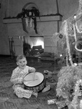 1950s Little Boy Playing Toy Drum by Christmas Tree and Fireplace