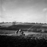 A Field in Hertfordshire  Being Ploughed by a Man on a Tractor
