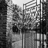 A Decorative Wrought-Iron Gate with Brick Gate Piers Stands Slightly Ajar