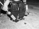 1940s-1950s Close-Up of Padded Goalie Shown Waist-Down Holding Stick with Puck in Front of Him
