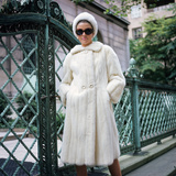 1960s Woman Wearing White Mink Fur Coat Hat Sunglasses by Wrought Iron Gate