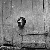 A Springer Spaniel Peering Out from a Small Circular Hole Cut into the Wooden Plank Door of a Barn