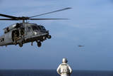 Sailor Watches an Air Force Hh-60G Pave Hawk Helicopter Prepare to Land