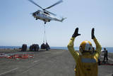 Aviation Boatswain's Mate Directs an SA-330J Puma Helicopter