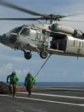 Airmen Run to Cover after Attaching Cargo Legs to an Mh-60S Sea Hawk