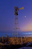Venus and Jupiter are Visible Behind an Old Farm Water Pump Windmill  Alberta  Canada