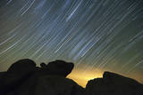 Light Pollution Illuminates the Sky and Star Tails Above Large Boulders