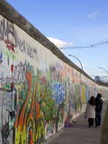 Couple Walking Along the East Side Gallery Berlin Wall Mural  Berlin  Germany  Europe
