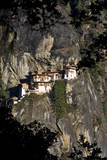 View Through a Forest Canopy to a Buddhist Monastery Perched on a Cliff Face in the Setting Sun