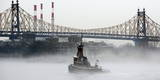 A Tug Boat Passes Along a Fog Shrouded the East River and the Ed Koch Queensboro Bridge in New York
