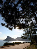 A Cyclist Rides Past the Sentinel Peak in Hout Bay Near Cape Town  South Africa