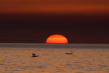 Fishermen Lay their Nets in the Sea as the Sun Sets