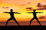 Yoga People Training and Meditating in Warrior Pose Outside by Beach at Sunrise or Sunset