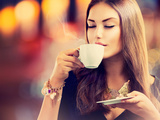 Beautiful Girl Drinking Tea or Coffee in Café