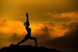 Silhouette of Woman Doing Yoga Meditation During Sunrise with Natural Golden Sunlight on Mountain