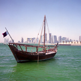 A Qatari Sailing Dhow  Called a Boom or Boum  with the National Flag Flying and the Doha Skyline