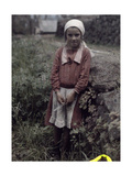 A Young Girl from a Farm Community Poses  Leaning Against a Rock