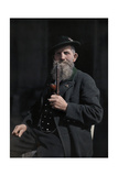 A Bearded Man Sits and Smokes His Pipes in This Informal Portrait