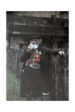 A Man Dressed in Berggeist Costume Smokes His Pipe Against the Fence