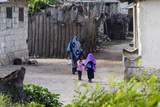 A Muslim Mother and Her Daughters Walking Through Lanes in an Island Village