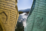 Sunlight Reflecting Off the Surface of an Alpine Rive Backlighting Prayer Flags Hanging from a Brid