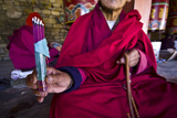 A Buddhist in Red Robes Displays Burning Dhoop Whilst Seated Beside Prayer Wheels