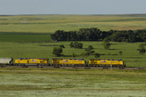 A Train Running Through a Vast Landscape of Fields and Prairies