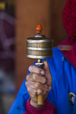 A Buddhist Spinning a Prayer Wheel for Prayers and Aspirations at a Memorial Chorten