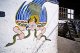 A Colorful Mural of Garuda Eating a Snake on the Wall of a Home Near a Buddhist Monastery