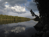 Heavy Clouds Casting Reflections into a Calm Lake Lined by Evergreen Trees