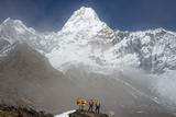 A Climbing Team Stand Looking Up at Ama Dablam in the Everest Region of Nepal