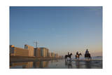 Three Cowboys Ride their Horses Along Virginia Beach at Sunrise