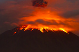 The Tungurahua Volcano Erupting at Night Flowing Lava Casts Glowing Reflections on the Clouds