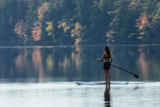 A Woman Paddleboarding in a Calm Pond Rimmed by Trees in Autumn Hues