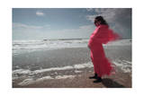 A Pregnant Woman Wearing a Flowing Pink Scarf and Dress Standing in the Wind on a Beach