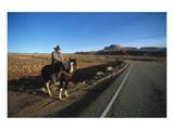 Cowboy on his horse on a highway near Hanksville  Utah  USA