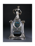 A Mantel Clock Surmounted by a Figure of an Elegant Lady